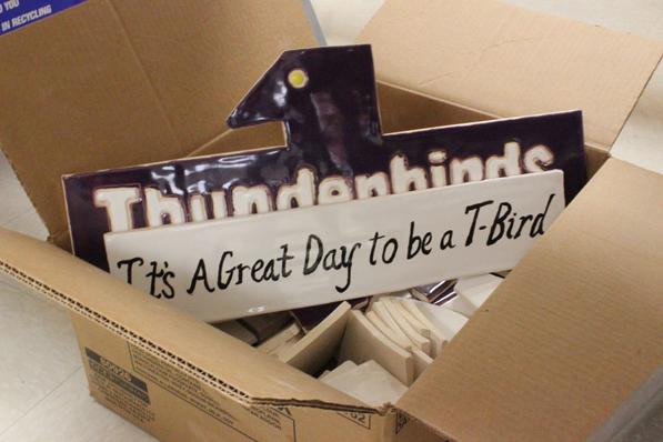 A Thunderbird for the new mosaic sits in a cardboard box with other tiles.